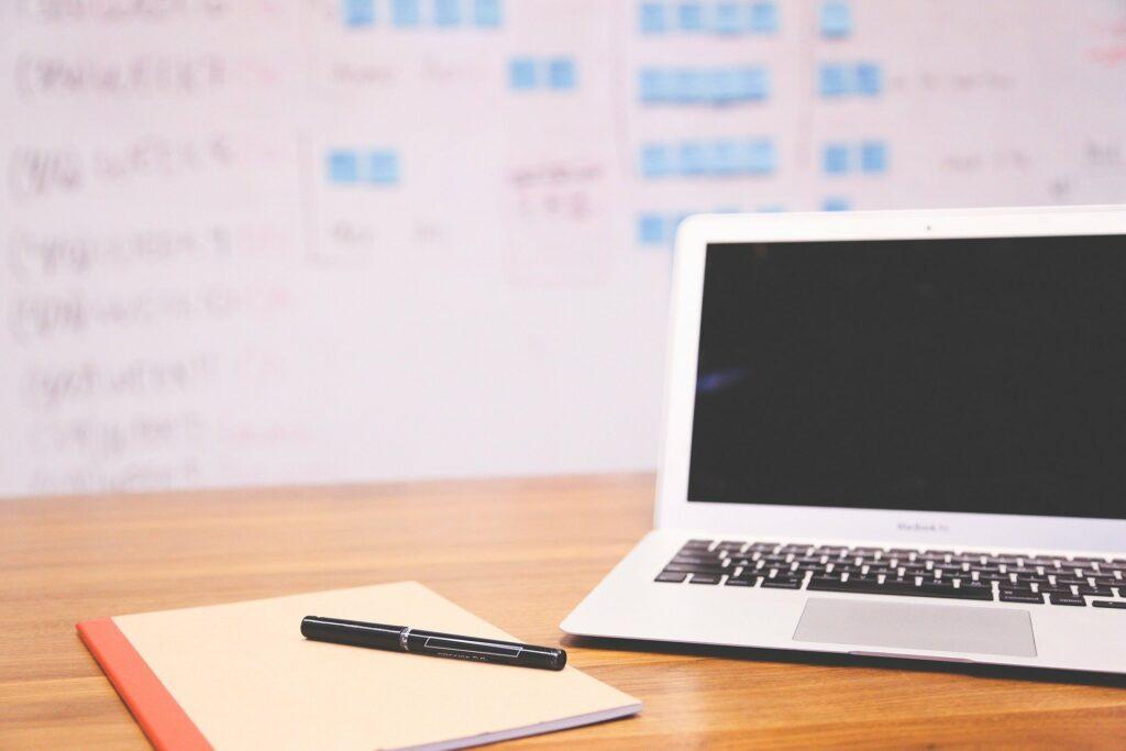Laptop und Schreibmaterial